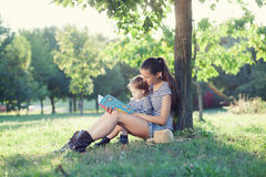 Stylish mother and toddler reading book at garden during summer fun Stock Photography