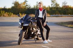 Stylish motorcyclist wears fashionable bikers clothes, white sportshoes, poses near her motorbike, has rest after long journey, en royalty free stock photography