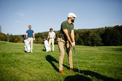 Golf player walking and carrying bag on course during summer gam royalty free stock photos