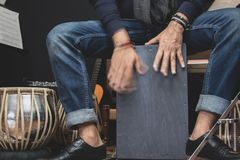 Stylish musician playing the Cajon drums. A stylish musician in denim and double monk shoes plays the Cajon, a Peruvian drum used commonly with Spanish Flamenco royalty free stock image