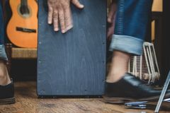 Stylish musician playing the Cajon drums. A stylish musician in denim and double monk shoes plays the Cajon, a Peruvian drum used commonly with Spanish Flamenco royalty free stock images