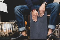 Stylish musician playing the Cajon drums. A stylish musician in denim and double monk shoes plays the Cajon, a Peruvian drum used commonly with Spanish Flamenco stock photography