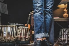 Stylish musician playing the Cajon drums. A stylish musician in denim and double monk shoes plays the Cajon, a Peruvian drum used commonly with Spanish Flamenco royalty free stock photo