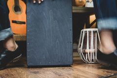 Stylish musician playing the Cajon drums. A stylish musician in denim and double monk shoes plays the Cajon, a Peruvian drum used commonly with Spanish Flamenco royalty free stock photos
