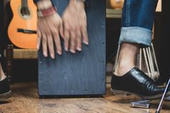 Stylish musician playing the Cajon drums. A stylish musician in denim and double monk shoes plays the Cajon, a Peruvian drum used commonly with Spanish Flamenco stock photos