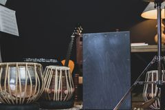 Stylish musician playing the Cajon drums. A stylish musician in denim and double monk shoes plays the Cajon, a Peruvian drum used commonly with Spanish Flamenco stock images