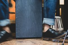 Stylish musician playing the Cajon drums. A stylish musician in denim and double monk shoes plays the Cajon, a Peruvian drum used commonly with Spain's royalty free stock image