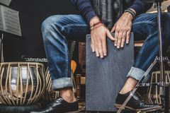 Stylish musician playing the Cajon drums. A stylish musician in denim and double monk shoes plays the Cajon, a Peruvian drum used commonly with Spain royalty free stock photo