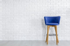 Stylish navy blue bar stool. With wooden legs against white brick wall in spacious room stock photography