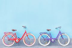 Stylish new bicycles near color. Wall outdoors Stock Photos