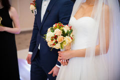 Stylish newlywed couple with bouquet at wedding reception Royalty Free Stock Photo