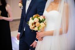 Stylish newlywed couple with bouquet at wedding reception Royalty Free Stock Photo