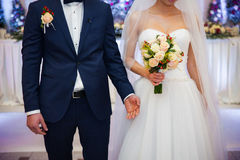 Stylish newlywed couple with bouquet at wedding reception Royalty Free Stock Photography