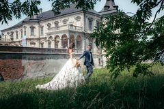 The stylish newlywed couple is holding hands while walking along the green forest at the background of the old house. Stock Images