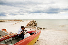 Stylish newlyweds sitting in a boat on the beach. Royalty Free Stock Photography