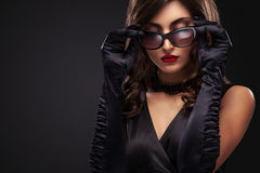 Stylish night flash fashion portrait of trendy casual young woman in black dress. Royalty Free Stock Image