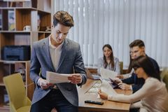 Stylish office worker in a jacket reads paper, leaning on a table, and on the background of his colleagues stock photos