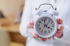Stylish office worker woman in glasses with a classic alarm clock in the hands on background of working colleagues stock photo