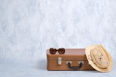 Stylish old fashioned accessories of hipster female traveller: vintage sunglasses, straw hat, leather suitcase on grey background. Concept of travel with carry stock photography