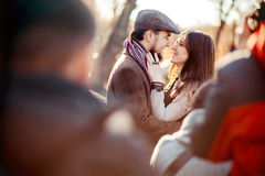 Stylish old fashioned couple among crowd looking at each other outdoors in backlight. Man wearing tweed flat cap, brown Stock Image