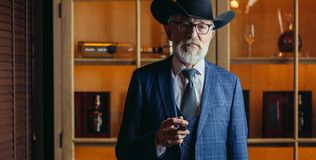 Stylish old man in wide brimmed hat and rich blue mens suit smok. Stylish old-aged dandy in wide brimmed hat and rich dark blue mens suit smoking cigar indoor stock images