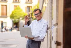 Stylish old man working on laptop surfing the internet in city outdoors in digital nomad Senior using modern technology Staying. Connected and entrepreneur royalty free stock image