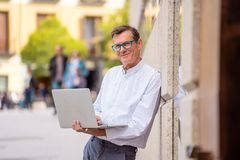 Stylish old man working on laptop surfing the internet in city outdoors in digital nomad Senior using modern technology Staying. Connected and entrepreneur royalty free stock photography