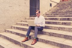 Stylish old man working on laptop surfing the internet sitting on stairs outdoors city in digital nomad Senior using modern. Technology Staying connected and royalty free stock images