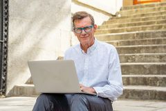 Stylish old man working on laptop surfing the internet sitting on stairs outdoors city in digital nomad Senior using modern. Technology Staying connected and royalty free stock photos