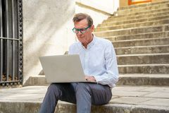 Stylish old man working on laptop surfing the internet sitting on stairs outdoors city in digital nomad Senior using modern. Technology Staying connected and stock photo