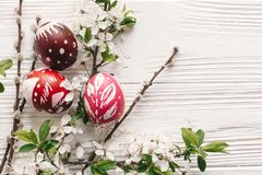 Stylish painted easter eggs on rustic wooden background with spring flowers and willow branches. happy easter greeting card flat. Lay. space for text. modern royalty free stock photo