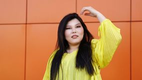 Stylish Pan-Asian girl posing outdoor. Beauty plus size pan-asian girl posing in front of bright wall background. Body Positivity Movement. Happiness lifestyle royalty free stock photo