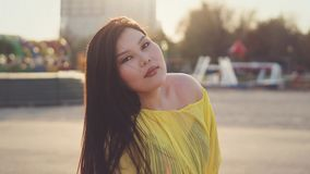 Stylish Pan-Asian girl posing outdoor. Portrait of attractive plus size pan-asian girl with long hair posing on amusement park background. She wears yellow royalty free stock photos