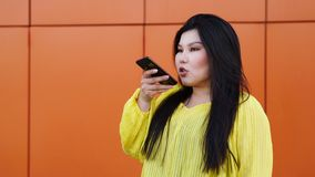 Stylish Pan-Asian girl posing outdoor. Stylish plus size pan-Asian girl recording voice message with smartphone. Woman sending audio message on cell phone on a stock images