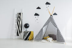 Stylish, patterned teepee in bedroom. Stylish,patterned teepee with a white teddy bear lying inside it, in a minimalist. scandinavian kid bedroom Royalty Free Stock Images