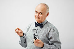 Stylish pensioner posing for picture. Portrait of confident bald senior man in striped shirt with bow tie holding eyeglasses, looking at camera with quizzical Stock Photo