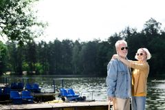Attractive couple of pensioners smiling while hugging on the pier. Stylish pensioners. Cheerful beautiful couple of pensioners smiling and looking stylish while Royalty Free Stock Photos