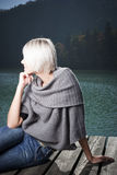 Stylish pensive woman on a wooden jetty Stock Photo