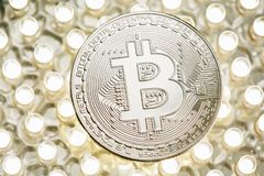 Stylish photo of Bitcoin silver coin on LED panel. Virtual cryptocurrency concept. stock images