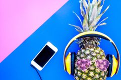 Stylish pineapple in sunglasses listen to music on the smartphone on blue and pink background top view copyspace. Stylish pineapple in sunglasses listen to music Stock Photography