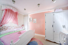 Stylish pink bedroom for girl. With white wardrobe, big bed and illuminated niche Stock Photography