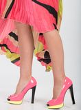 Stylish pink high heels with a green yellow trim. Partial image of a woman's legs and high heels royalty free stock photography