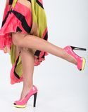 Stylish pink high heels with a green yellow trim. Partial image of a woman's legs and high heels stock photos