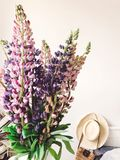 Stylish pink and purple lupine in vase on background of trendy straw bag and hat on stylish white bed. Hello spring. Happy Mothers. Day. Countryside living stock image