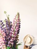 Stylish pink and purple lupine in vase on background of trendy straw bag and hat on stylish white bed. Hello spring. Happy Mothers. Day. Countryside living royalty free stock photo