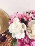 Stylish pink and white peonies in vase and trendy straw bag and hat on stylish white nightstand near bed. Hello spring. Happy. Mothers day. Girly image royalty free stock images