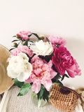 Stylish pink and white peonies in vase and trendy straw bag and hat on stylish white nightstand near bed. Hello spring. Happy. Mothers day. Girly image stock images