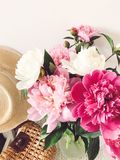 Stylish pink and white peonies in vase and trendy straw bag and hat on stylish white nightstand near bed. Hello spring. Happy. Mothers day. Girly image royalty free stock image
