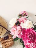 Stylish pink and white peonies in vase and trendy straw bag and hat on stylish white nightstand near bed. Hello spring. Happy. Mothers day. Girly image stock photography