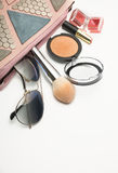 Stylish pink woman`s bag with mineral powder, lip gloss, sunglas Royalty Free Stock Photography
